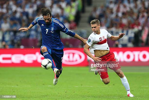 Giorgos Samaras of Greece controls the ball ahead of Lukasz Piszczek of Poland during the UEFA EURO 2012 group A match between Poland and Greece at...