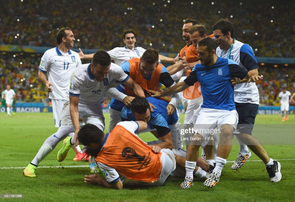 Giorgos Samaras of Greece is mobbed by team mates after scoring his team's second goal from the penalty spot during the 2014 FIFA World Cup Brazil Group C match between Greece and Cote D'Ivoire at Estadio Castelao on June 24, 2014 in Fortaleza, Brazil.