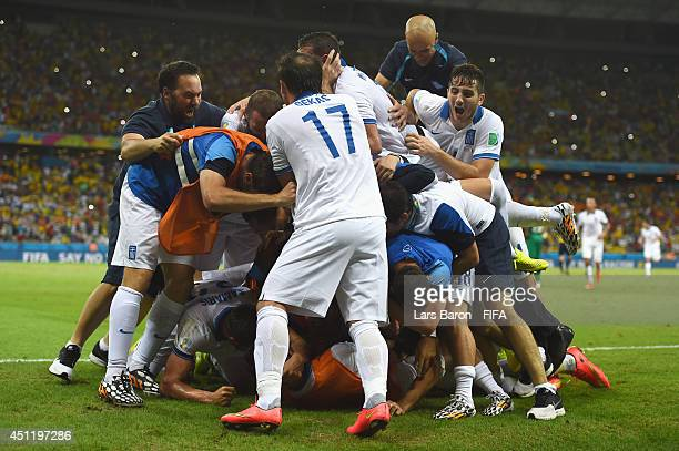 Giorgos Samaras of Greece is mobbed by team mates after scoring his team's second goal from the penalty spot during the 2014 FIFA World Cup Brazil...