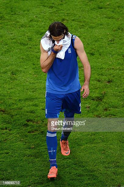 Giorgos Samaras of Greece leaves the field dejected after defeat in the UEFA EURO 2012 quarter final match between Germany and Greece at The...