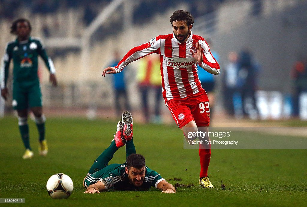Giorgos Seitaridis of Panathinaikos falls as Djamel Abdoun of Olympiacos attacks during the Superleague match between Panathinaikos FC and Olympiacos Piraeus at OAKA Stadium on December 9, 2012 in Athens, Greece.