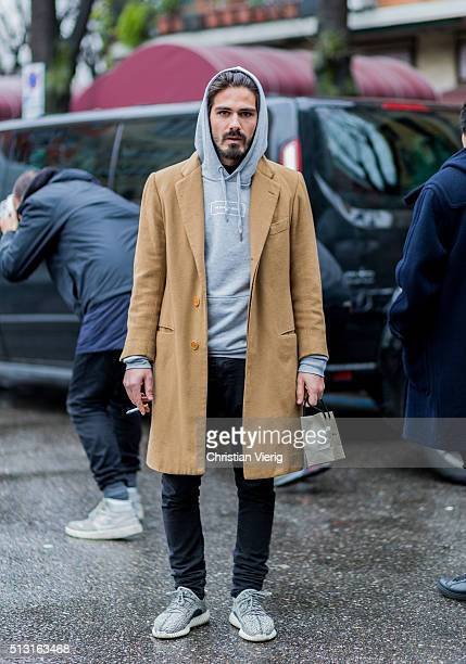 Giotto Calendoli wearing a The Classy Shop grey hoody and a wool coat seen outside Giorgio Armani during Milan Fashion Week Fall/Winter 2016/17 on...