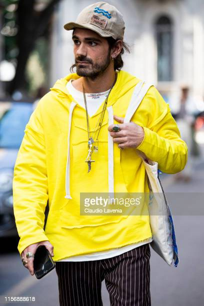 Giotto Calendoli wearing a yellow sweatshirt brown striped pants and beige hat is seen outside Giorgio Armani show during the Milan Men's Fashion...