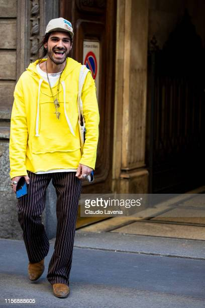 Giotto Calendoli wearing a yellow sweatshirt brown striped pants tan boots and beige hat is seen outside Giorgio Armani show during the Milan Men's...