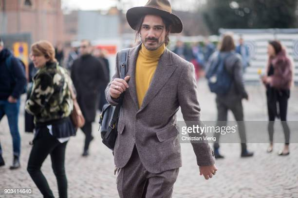 Giotto Calendoli wearing hat mustard turtleneck suit is seen during the 93 Pitti Immagine Uomo at Fortezza Da Basso on January 10 2018 in Florence...
