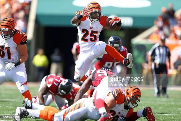 Giovani Bernard of the Cincinnati Bengals jumps over Jonathan Massaquoi of the Atlanta Falcons during the second quarter at Paul Brown Stadium on...