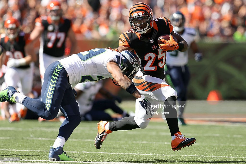 Giovani Bernard #25 of the Cincinnati Bengals stiff arms Earl Thomas #29 of the Seattle Seahawks while running with the ball during the second quarter at Paul Brown Stadium on October 11, 2015 in Cincinnati, Ohio.