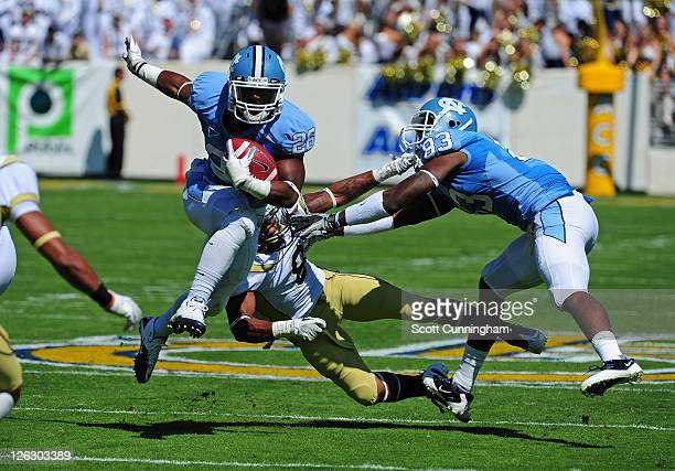 Giovani Bernard of the North Carolina Tar Heels carries the ball with a block by Dwight Jones against Louis Young of the Georgia Tech Yellow Jackets...