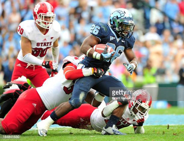 Giovani Bernard of the North Carolina Tar Heels drags Ricky Dowdy and Dontae Johnson of the North Carolina State Wolfpack for extra yardage during...