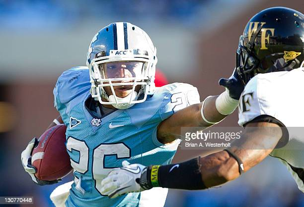 Giovani Bernard of the North Carolina Tar Heels stiff arms Merrill Noel of the Wake Forest Demon Deacons on his way to scoring a touchdown at Kenan...
