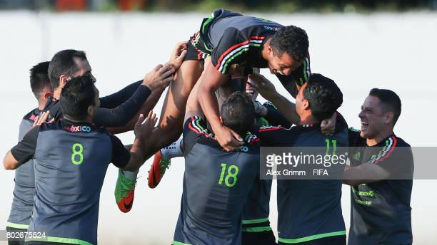Giovani dos Santos is lifted up into the air by his team mates during a Mexico press conference at Fisht Olympic stadium ahead of their FIFA...