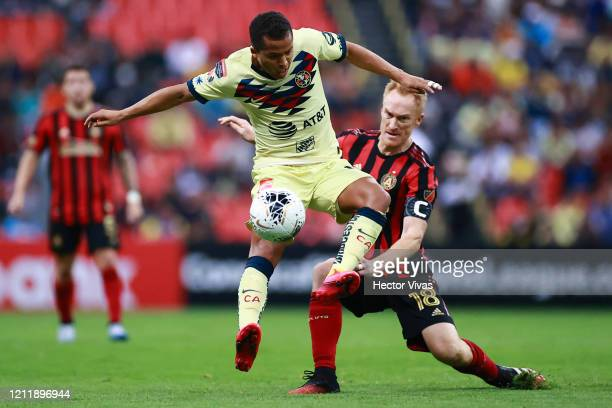 Giovani Dos Santos of America struggles for the ball against Jeff Larentowicz of Atlanta United during a quarter final first leg match between Club...