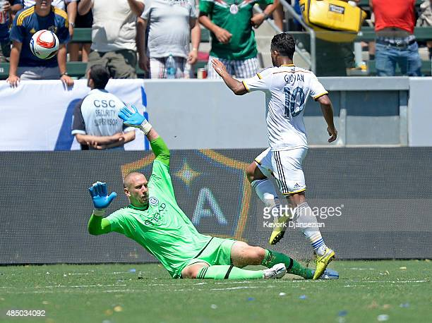 Giovani Dos Santos of Los Angeles Galaxy kicks the ball over goalkeeper Josh Saunders of New York City FC to score a goal during the second half at...