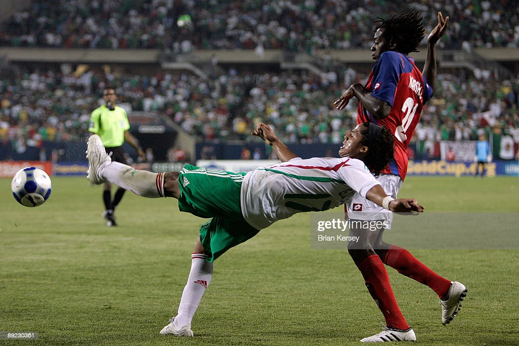 Giovani Dos Santos #17 of Mexico attempts to control the ball against Dennis Marshall #20 of Costa Rica during their CONCACAF Cup Semifinal match at Soldier Field on July 23, 2009 in Chicago, Illinois.