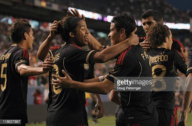 Giovani Dos Santos of Mexico celebrates his second goal of the game with Pablo Barrera in the 30th minute against New Zealand at INVESCO Field at...