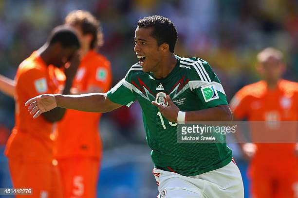 Giovani dos Santos of Mexico celebrates scoring his team's first goal during the 2014 FIFA World Cup Brazil Round of 16 match between Netherlands and...