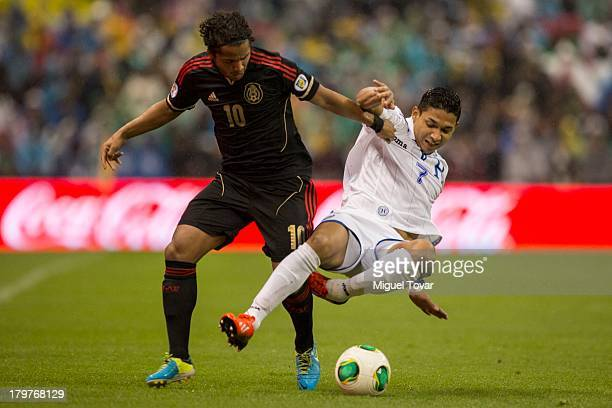 Giovani Dos Santos of Mexico fights for the ball with Emilio Izaguirre of Honduras during a match between Mexico and Honduras as part of the 15th...