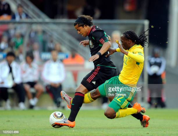 Giovani Dos Santos of Mexico is tackled by Reneilwe Letsholonyane of South Africa during the 2010 FIFA World Cup South Africa Group A match between...