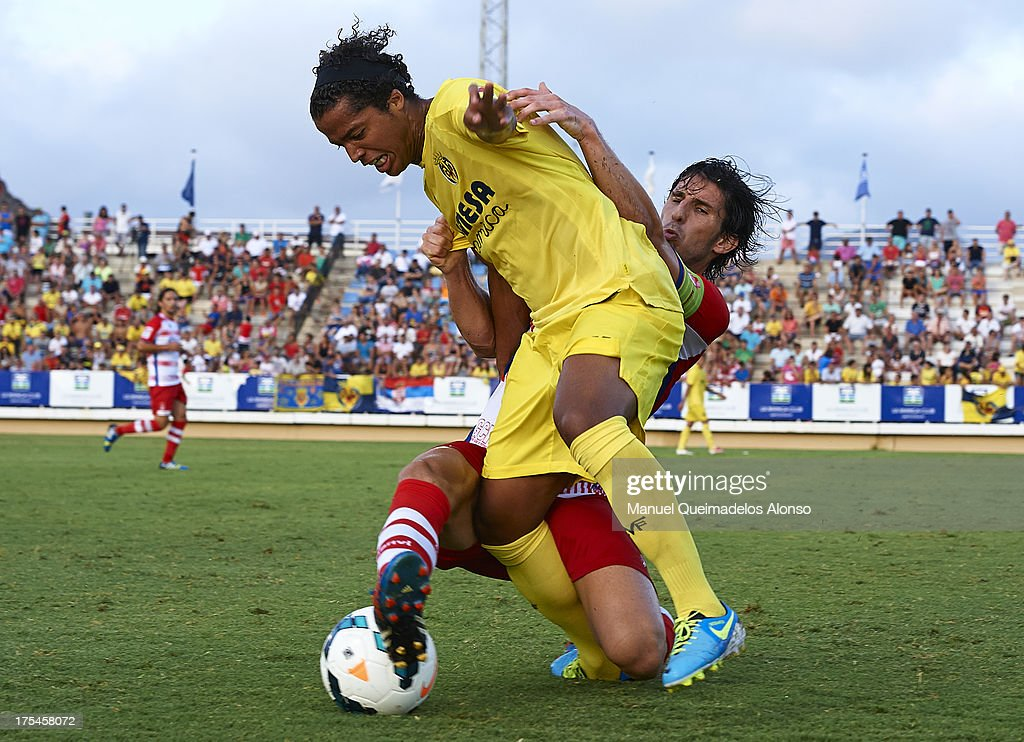 Giovani Dos Santos (L) of Villarreal is tackled by Diego Mainz of Granada during a friendly match between Villarreal CF and Granada FC at La Manga Club on August 03, 2013 in La Manga, Spain.