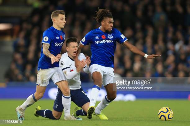 Giovani Lo Celso of Spurs is squeezed out by Lucas Digne of Everton and Alex Iwobi of Everton during the Premier League match between Everton FC and...