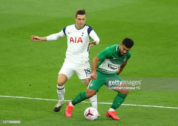 Giovani Lo Celso of Tottenham Hotspur battles for possession with Mohammad Abu Fani of Maccabi Haifa during the UEFA Europa League playoff match...