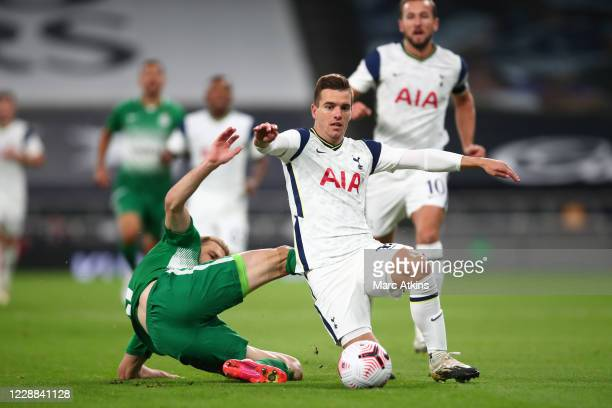 Giovani Lo Celso of Tottenham Hotspur in action with Bogdan Planic of Maccabi Haifa during the UEFA Europa League playoff match between Tottenham...