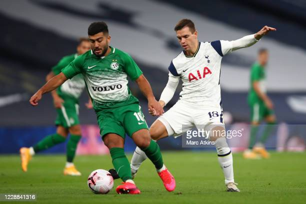 Giovani Lo Celso of Tottenham Hotspur in action with Mohammad Abu Fani of Maccabi Haifa during the UEFA Europa League playoff match between Tottenham...