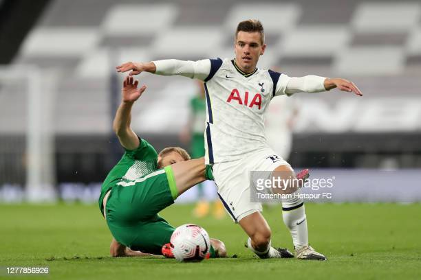 Giovani Lo Celso of Tottenham Hotspur is challenged by Bogdan Planic of Maccabi Haifa during the UEFA Europa League playoff match between Tottenham...