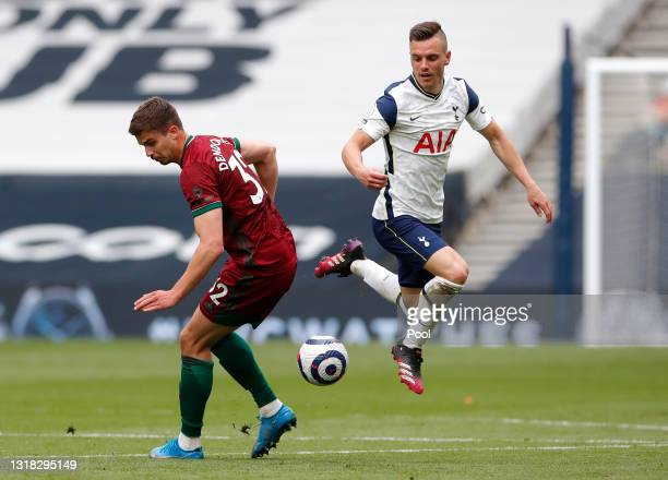Giovani Lo Celso of Tottenham Hotspur is challenged by Leander Dendoncker of Wolverhampton Wanderers during the Premier League match between...