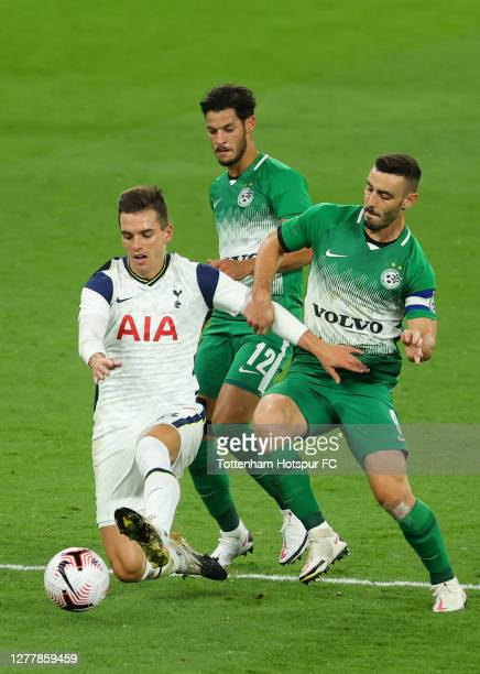 Giovani Lo Celso of Tottenham Hotspur is challenged by Sun Menahem and Neta Lavi of Maccabi Haifa during the UEFA Europa League playoff match between...