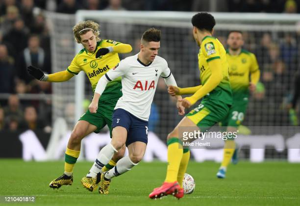 Giovani Lo Celso of Tottenham Hotspur is challenged by Todd Cantwell and Jamal Lewis of Norwich City during the FA Cup Fifth Round match between...