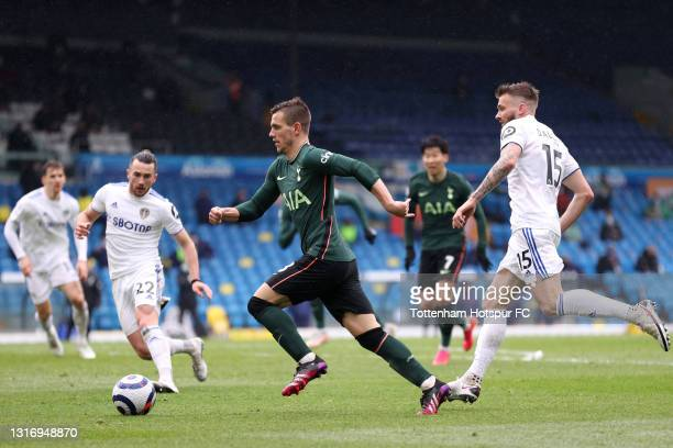 Giovani Lo Celso of Tottenham Hotspur runs with the ball whilst under pressure from Stuart Dallas of Leeds United during the Premier League match...
