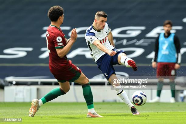 Giovani Lo Celso of Tottenham Hotspur shoots whilst under pressure from Ki-Jana Hoever of Wolverhampton Wanderers during the Premier League match...