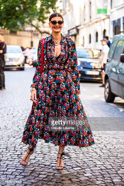 Giovanna Battaglia Engelbert, wearing a floral print long dress, black heels and red Valentino bag, is seen outside VALENTINO show during Paris...