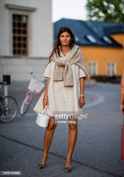 Giovanna Battaglia Engelbert wearing creme white dress, white bag, knit over her shoulders seen during Stockholm Runway SS19 on August 29, 2018 in...