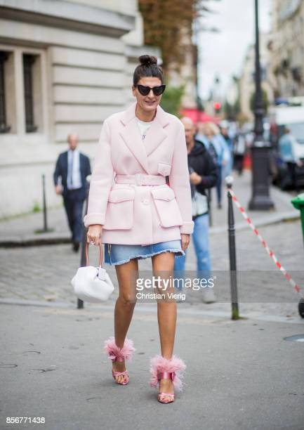 Giovanna Battaglia Engelbert wearing pink coat denim mini skirt seen outside Sacai during Paris Fashion Week Spring/Summer 2018 on October 2 2017 in...