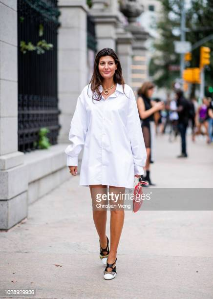 Giovanna Battaglia Engelbert wearing white dress, heels, red heart bag with NY print is seen outside Tory Burch during New York Fashion Week...