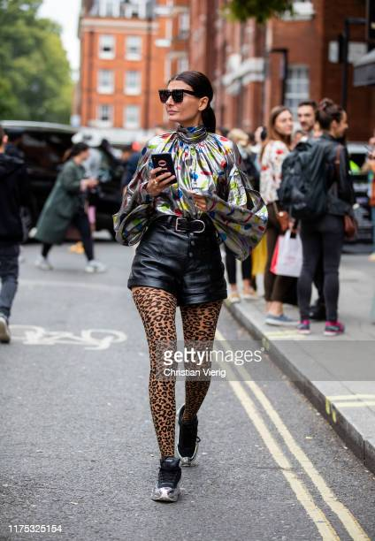 Giovanna Battaglia is seen wearing silver top black shorts leggings with animal print outside JW Anderson during London Fashion Week September 2019...