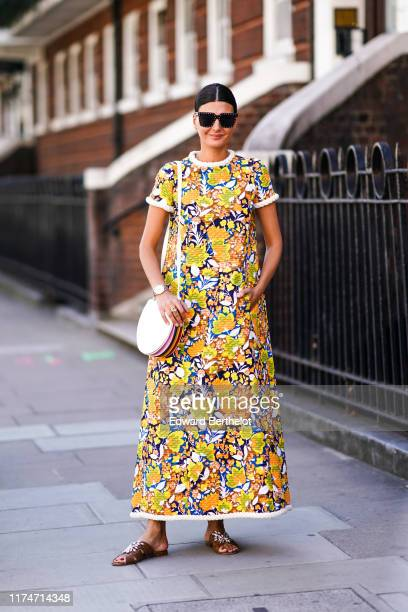 Giovanna Battaglia wears a colored floral print dress, sunglasses, a bag, brown sandals, during London Fashion Week September 2019 on September 14,...