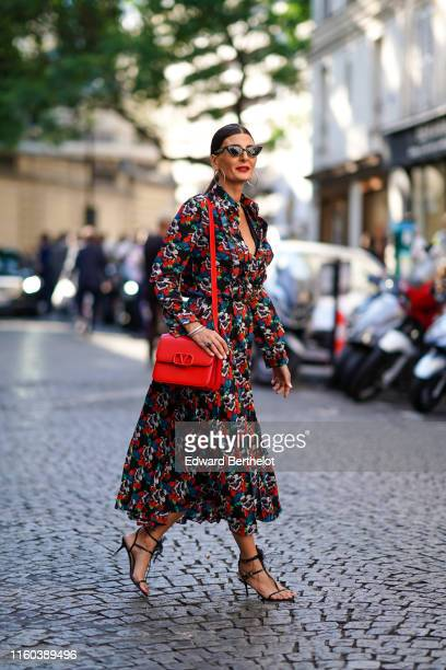 Giovanna Battaglia wears a multicolor floral print dress a red Valentino bag heels shoes sunglasses earrings outside Valentino during Paris Fashion...