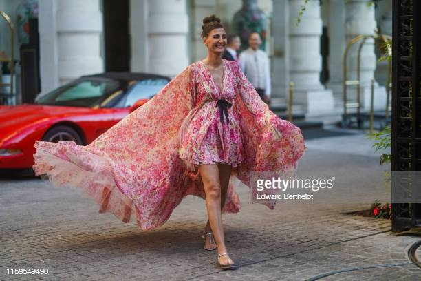 Giovanna Battaglia wears a pink floral print large flowing dress with a long cape, outside Giambattista Valli, during Paris Fashion Week -Haute...