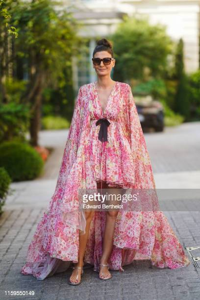 Giovanna Battaglia wears a pink floral print large flowing dress with a long cape outside Giambattista Valli during Paris Fashion Week Haute Couture...
