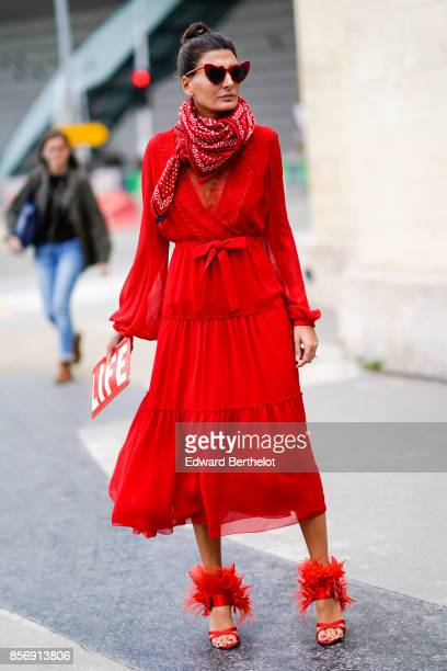 Giovanna Battaglia wears a red dress a clutch outside Giambattista Valli during Paris Fashion Week Womenswear Spring/Summer 2018 on October 2 2017 in...