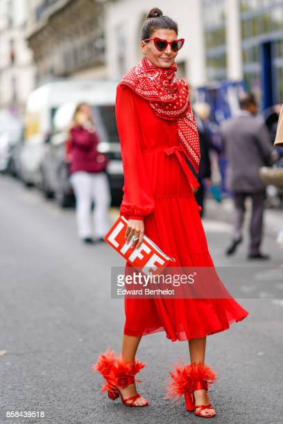 Giovanna Battaglia wears a red dress a red scarf red heart sunglasses a red LIFE clutch outside Giambattista Valli during Paris Fashion Week...