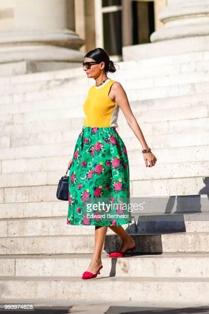 Giovanna Battaglia wears a yellow sleeveless top a green flower print skirt a bag pink shoes outside Fendi during Paris Fashion Week Haute Couture...