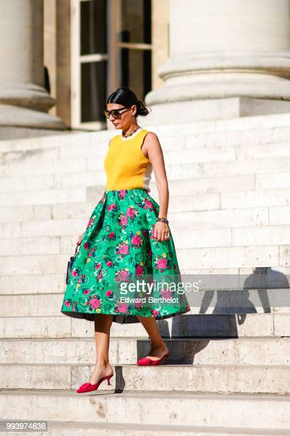 Giovanna Battaglia wears a yellow sleeveless top a green flower print skirt a bag pink shoes outside Fendi during Paris Fashion Week Haute Couture...