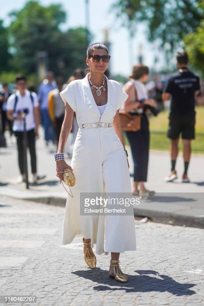Giovanna Battaglia wears sunglasses a Chanel white dress necklace bracelets a yellow clutch golden shoes outside Chanel during Paris Fashion Week...