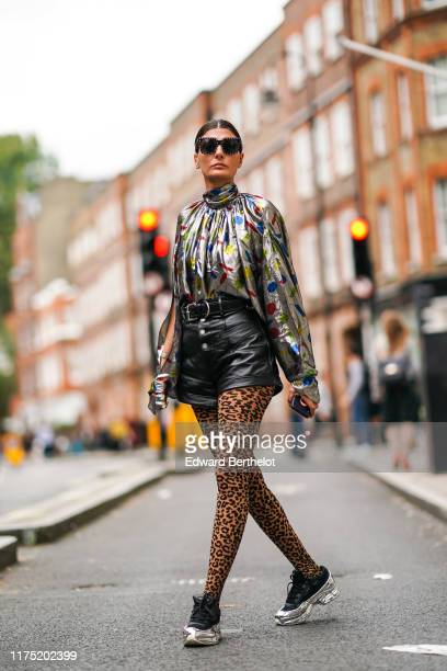 Giovanna Battaglia wears sunglasses a shiny glitter lustrous turtleneck top with colored printed features a belt a black leather skirt leopard print...