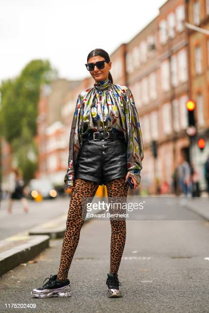 Giovanna Battaglia wears sunglasses, a shiny glitter lustrous turtleneck top with colored printed features, a belt, a black leather skirt, leopard...
