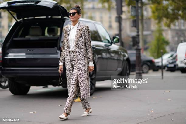 Giovanna Battaglia wears sunglasses a white shirt a leopard print coat leopard print pants white moccasins outside the Dries Van Noten show during...